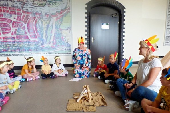 przedszkolaki siedzą wokół sztucznego ogniska, nauczycielka czyta list odWodza