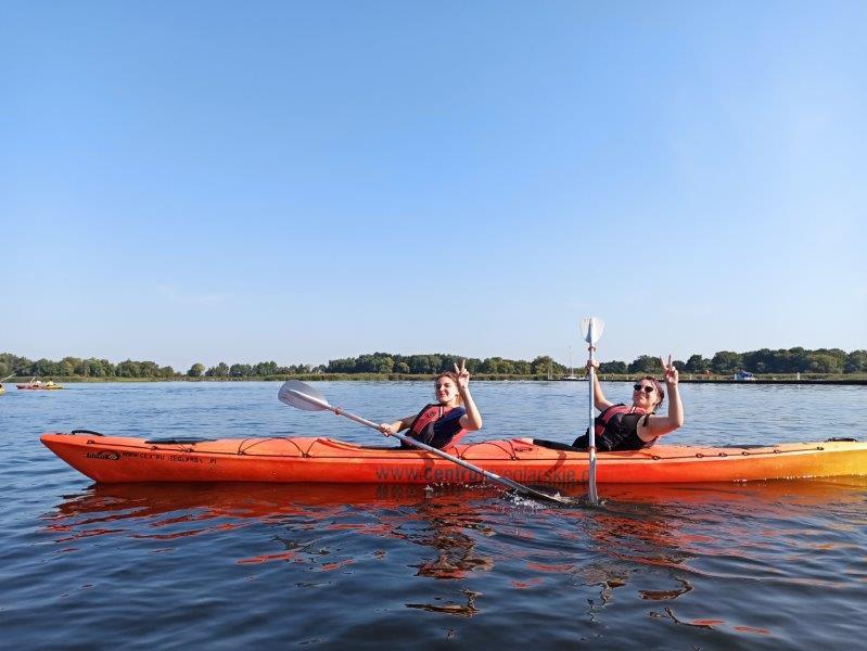 dwie uczennice Szkolnego Koła Edukacji Morskiej zTechnikum Ekonomicznego nawodzie wpomarańczowym kajaku