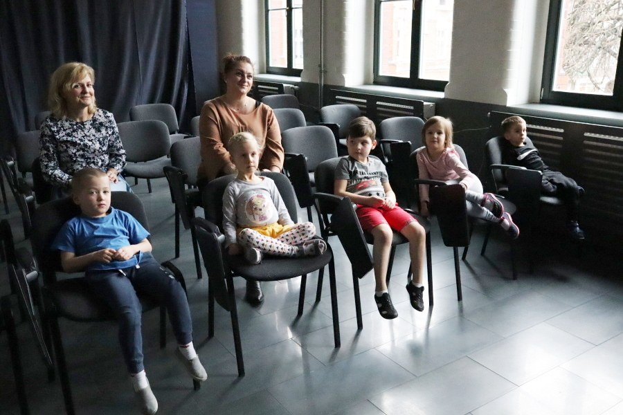 przedszkolaki siedzące na krzesłach z tyłu nauczycielki