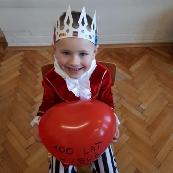 chłopiec wstroju króla trzymający serce balonowe