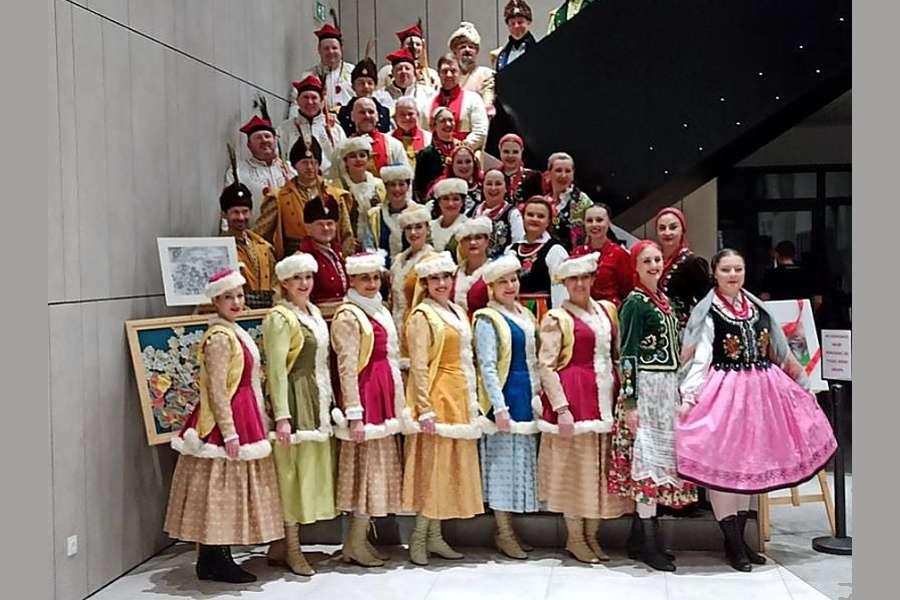 na zdjęciu widać ustawionych kaskadowo tancerzy w strojach ludowych pozujących do zdjęcia