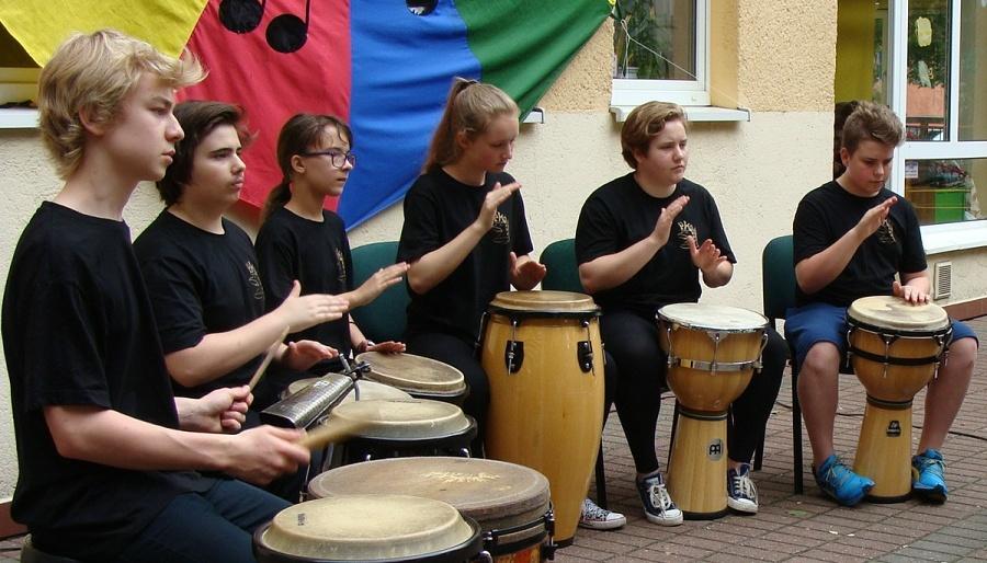 fotografia przedstawia sześcioro uczniów wczarnych strojach grających wplenerze naróżnych etnicznych instrumentach perkusyjnych.