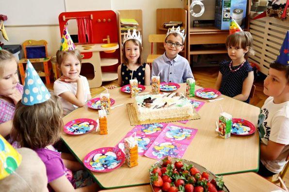 dzieci siedzące przy stole zesmakołykami