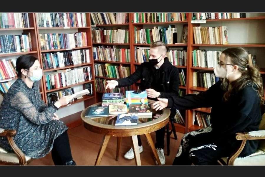 trzy osoby siedzące w maseczkach przy ogrągłym stoliku, w tle regały z książkami