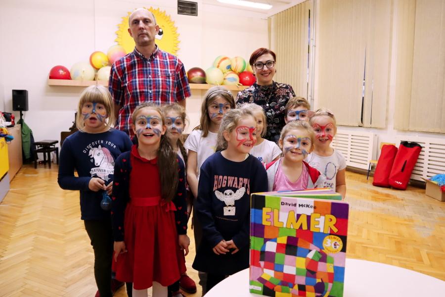 dzieci pozują do zdjęcia z nauczycielami, na pierwszym planie książka ELMER