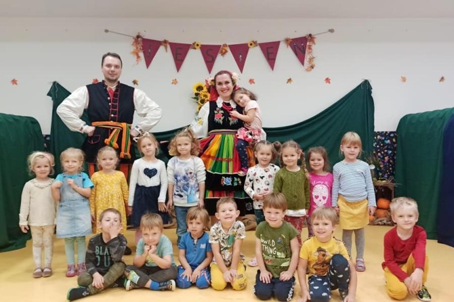 Grupa dzieci z opiekunami w strojach ludowych