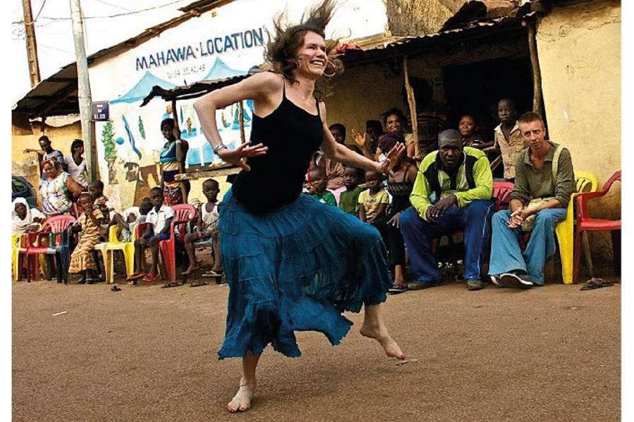 zdjęcie tańczącej kobiety w tle siedziący ciemnoskórzy ludzie