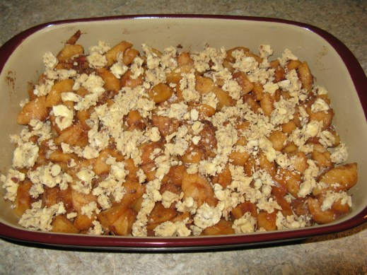 Filling with crumble topping, before going into the oven.