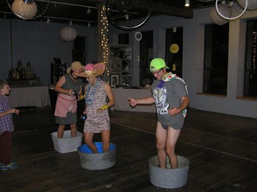 My sister, sister in-law and brother in-law doing their washtub dance with the addition of props. I don't know where this tradition came from, but it's been in our family that if a younger sibling gets married before an older sibling, they (the older siblings) have to dance in a washtub at the wedding. As you can see, my crazy bro in-law took off his pants. He even changed his shirt for the dance to a wolf one because it was wolf week. Also, none of them knew about this beforehand. It was pretty epic and people were even giving Nick money. He made over $20!