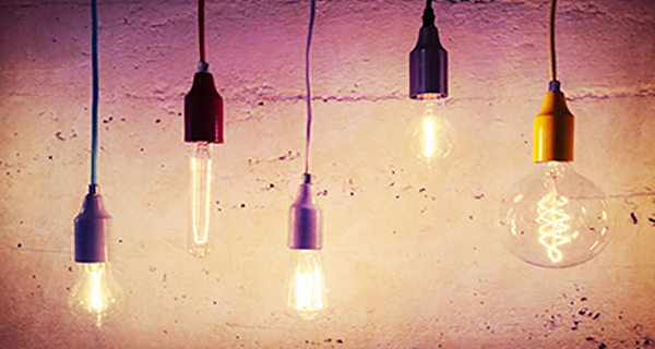 Illuminated light bulbs on concrete wall background. Industrial design.