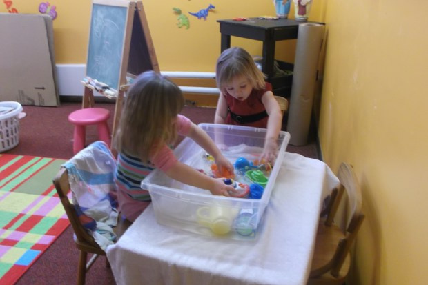 Two girls in a classroom playing with toys in a clear tub