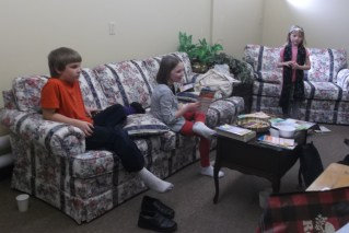 A boy and two girls sitting on a couch and loveseat in their Sunday school classroom