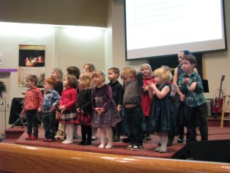 A group young children on stage participating in a Sunday school Christmas program