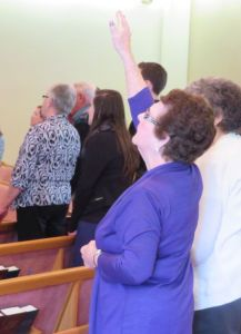 Woman raising her right arm in worship.