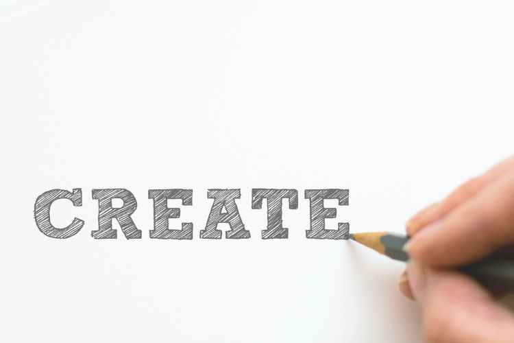 Artist colouring in the word create