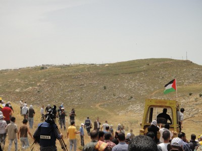 Bulldozer working Palestinian land accompanied by peaceful protesters. Illegal settlement outpost visible on hill
