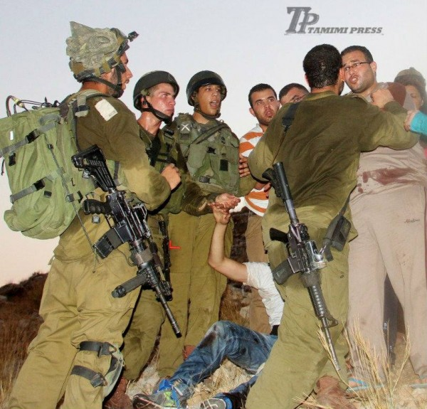 Israeli soldiers preventing people from aiding Mohammad Tamimi after he was shot (Photo by Tamimi Press)
