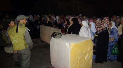 Palestinian women waiting in the queu for Israeli soldiers to let them through the checkpoint (Photo by ISM)