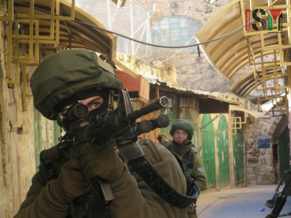 Israeli soldier 'ordering' Palestinians to stop by pointing his gun