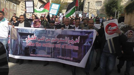 Demonstrators marching under the banner of 'take the settlers out of Hebron'