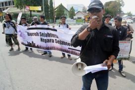 Ketua Aliansi Jurnalis Independen (AJI) Palu, Riski Maruto (depan) membacakan puisi pada peringatan Hari Buruh Internasional (May Day) di Palu, Sulawesi Tengah, Kamis (1/5).