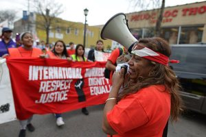 March of workers on May Day lead by woman with megaphone