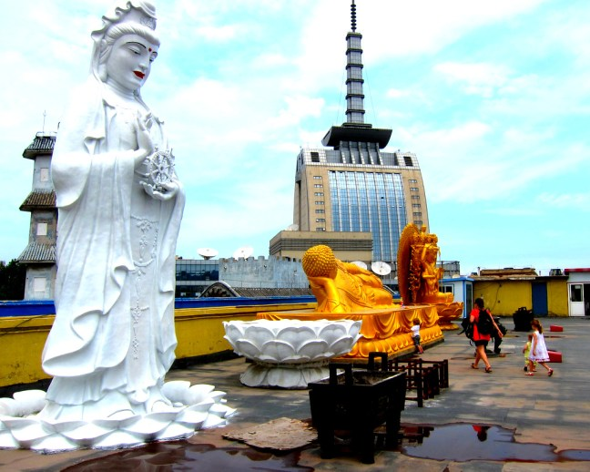 Large Buddha statues contrasted with t.v. building