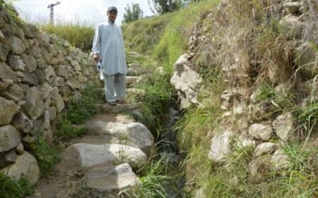 Inayat Karim, a mountain farming expert with the Baltit Rural Support Organisation, stands beside a reinforced water channel in Karimabad village, northern Pakistan. TRF/Saleem Shaikh