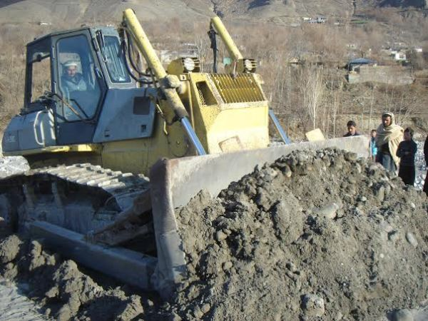 DC Chitral operating an earth mover to symbolically inaugurate the project