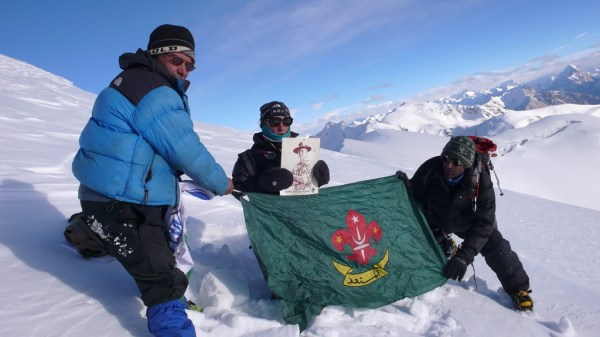Mohsin holding the portrait of Lord Baden Powell, the founder of Scouting movement, on top of the Minglik Sar peak