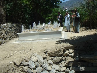People offering prayers at the grave of the murdered family members