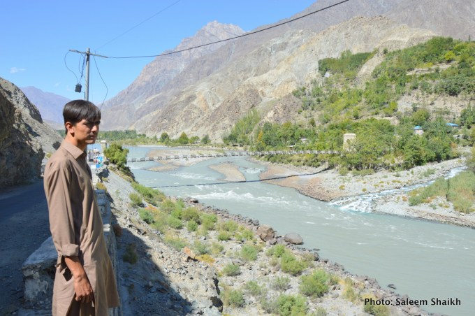 A boy looks at Gizer river, main tributary of the Indus river in picturesque valley of Gizer district, Pakistan's north. The locals say the river often gets swollen and pose serious risk to different mountain communities on its either side as local temperature continue to rise, causing paced-up glacial melt which generates flash floods. Photo credit: Saleem Shaikh