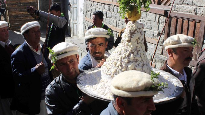 Locals carrying a traditional dish