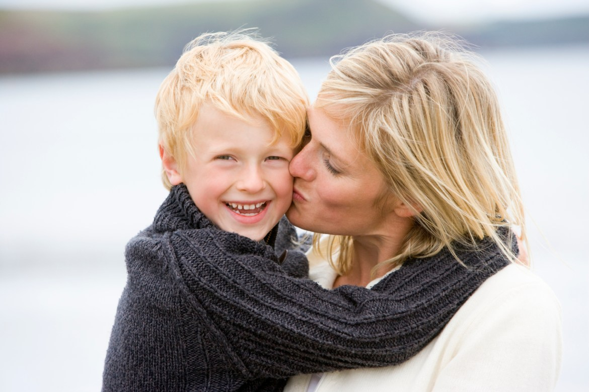 Mom kissing smiling son