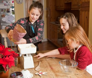 three girl pouring flour getting ready to bake some cookies