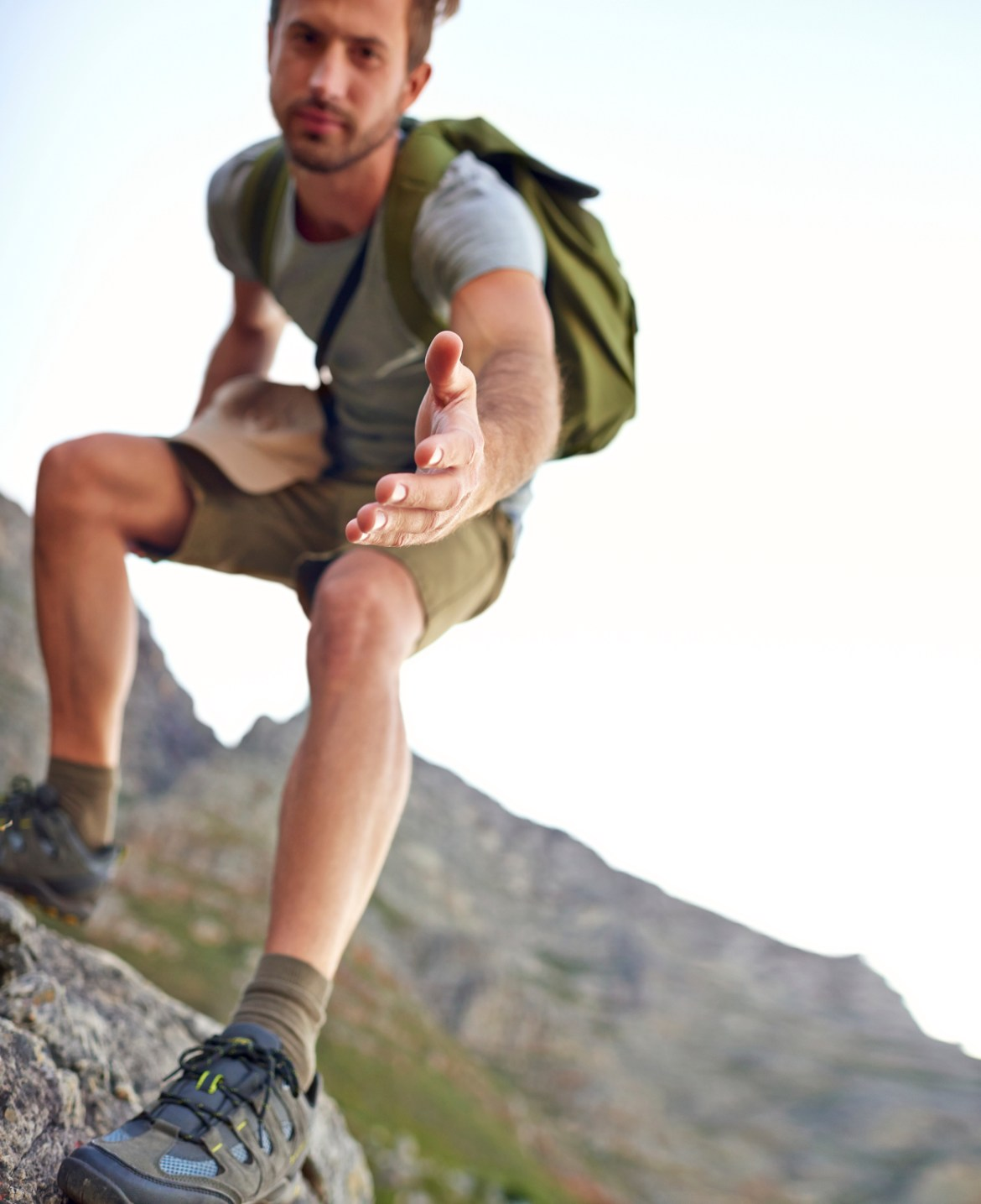 Man hiking on hill, reaching out to help someone up