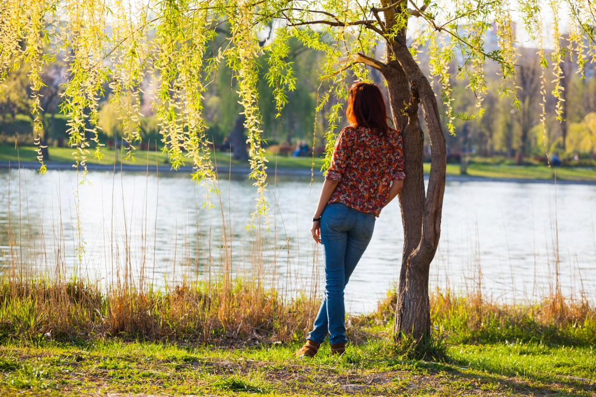 woman leaning against a tree, watching the river