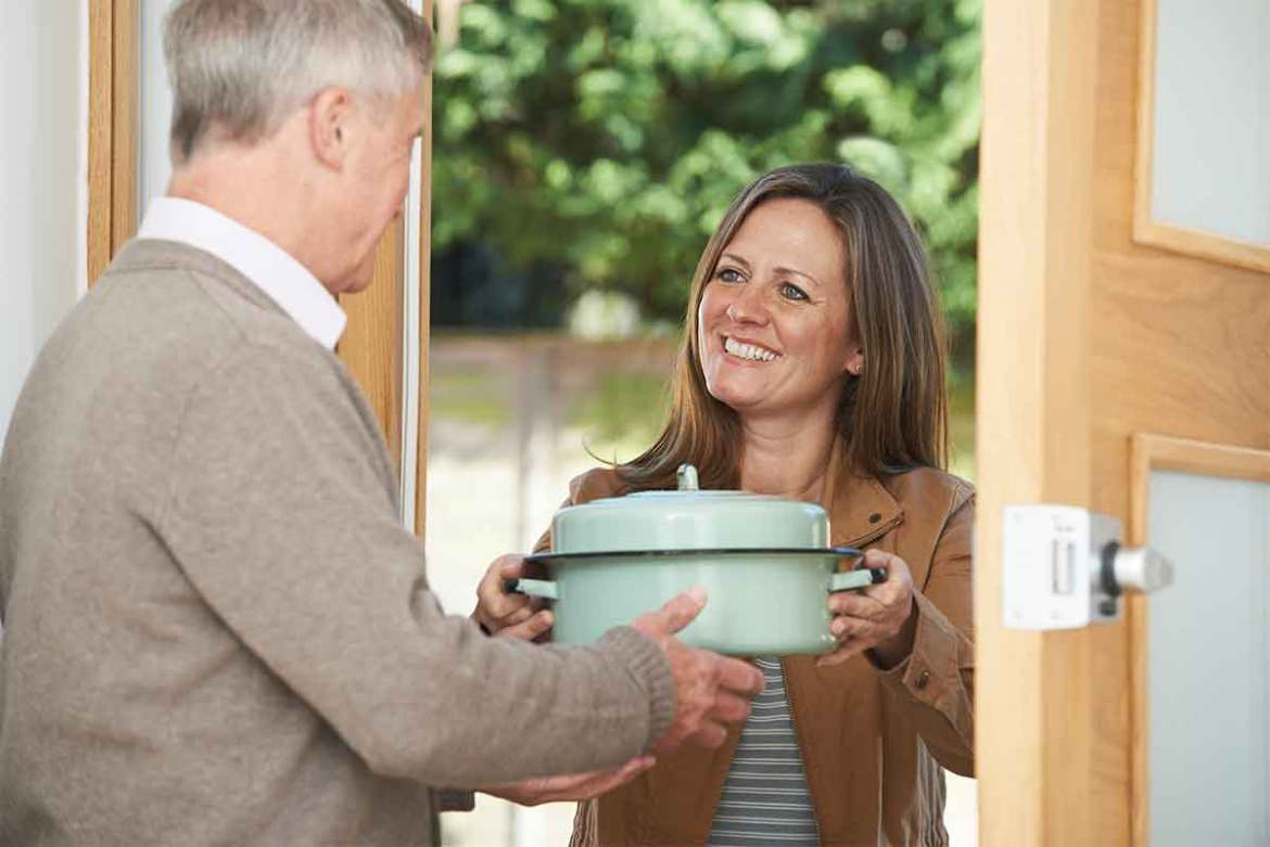 Lady bringing dinner to older man