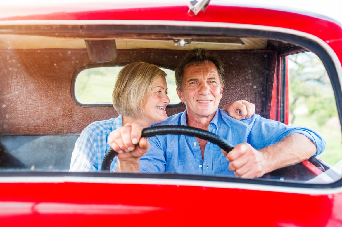 Senior couple in vintage red car