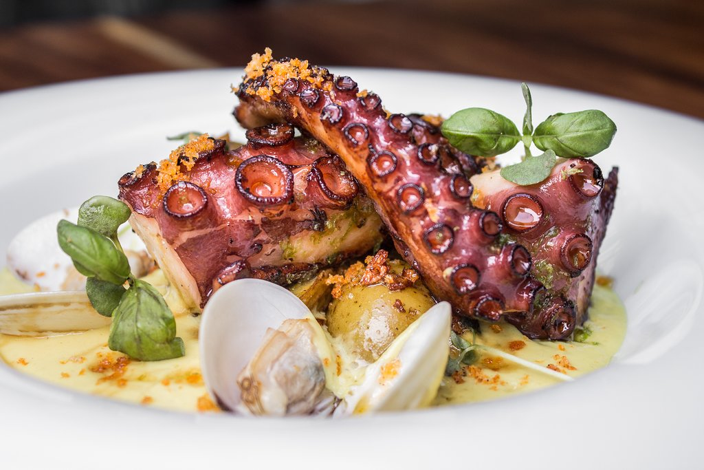 """""""Burning carbon"""" is veloute charcoal octopus with aji panca and sauteed clams."""