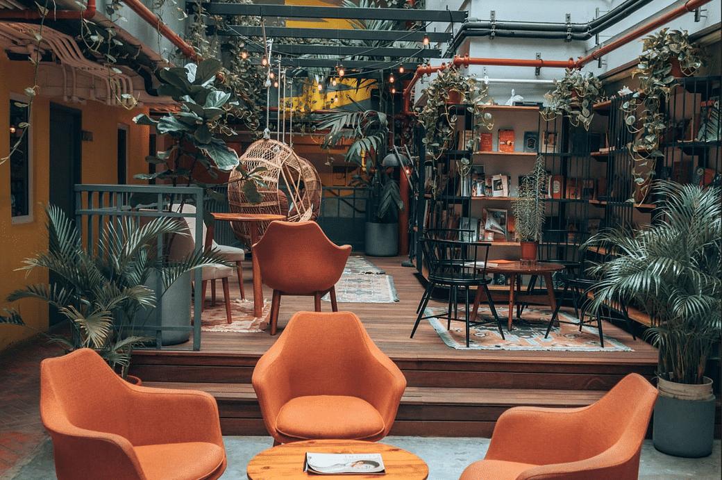 área común en Selina Casco Viejo con muchas plantas, libros, mesas y sillas