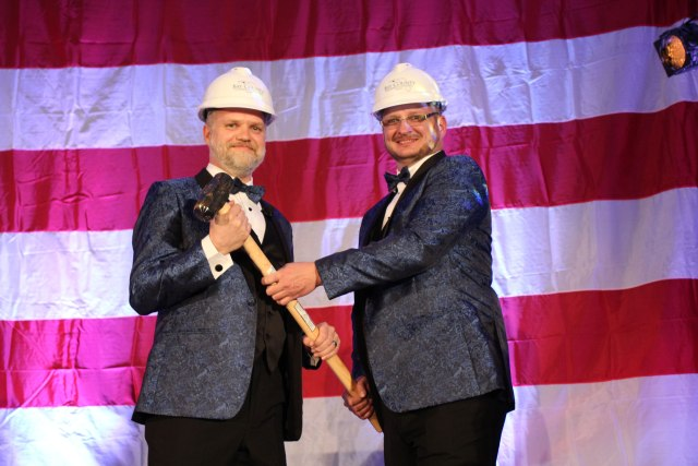 """2018 Chair of the Board, Will Cramer, """"passes the gavel"""" to incoming 2019 Chair of the Board, Doug Moore, at the 2019 Annual Dinner and Awards Ceremony."""