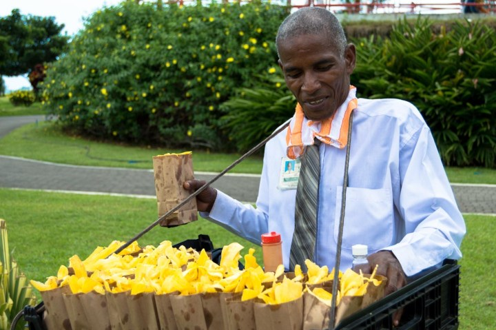 A street vendor selling bags of homemade plantain chips for $1.
