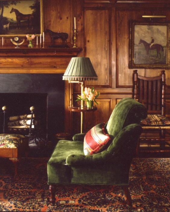 A green velvet sofa in a wood panelled room and a lamp with a pleated shade.