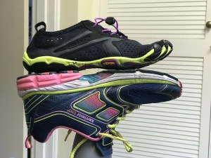 a barefoot running shoe standing on the sole of an upside-down normal running shoe