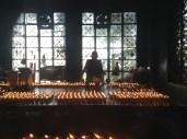 A monk lighting prayer candle at Tsuglagkhang