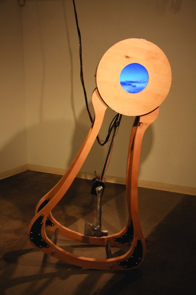 "The piece uses the environmental phrase ""tipping point"" to create an uncomfortable situation where the sculpture appears to almost fall over. The piece uses MAX programming and a Wii remote to keep the video water level while the structure rocks back and forth with the axes' counterbalancing force."