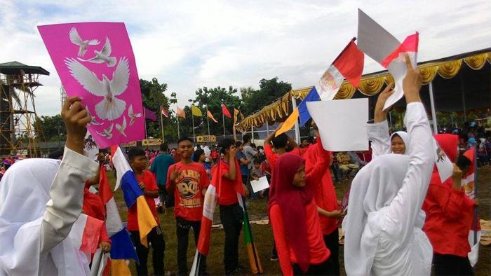 Para pelajar muslimah berjilbab membawa poster burung merpati dalam acara baksos di Bekasi