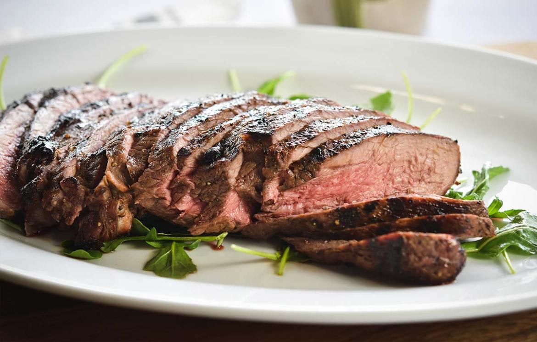 sliced steak with arugula salad