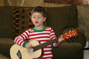 Holden with his new acoustic guitar. We get lots of serenades now. They're awesome.